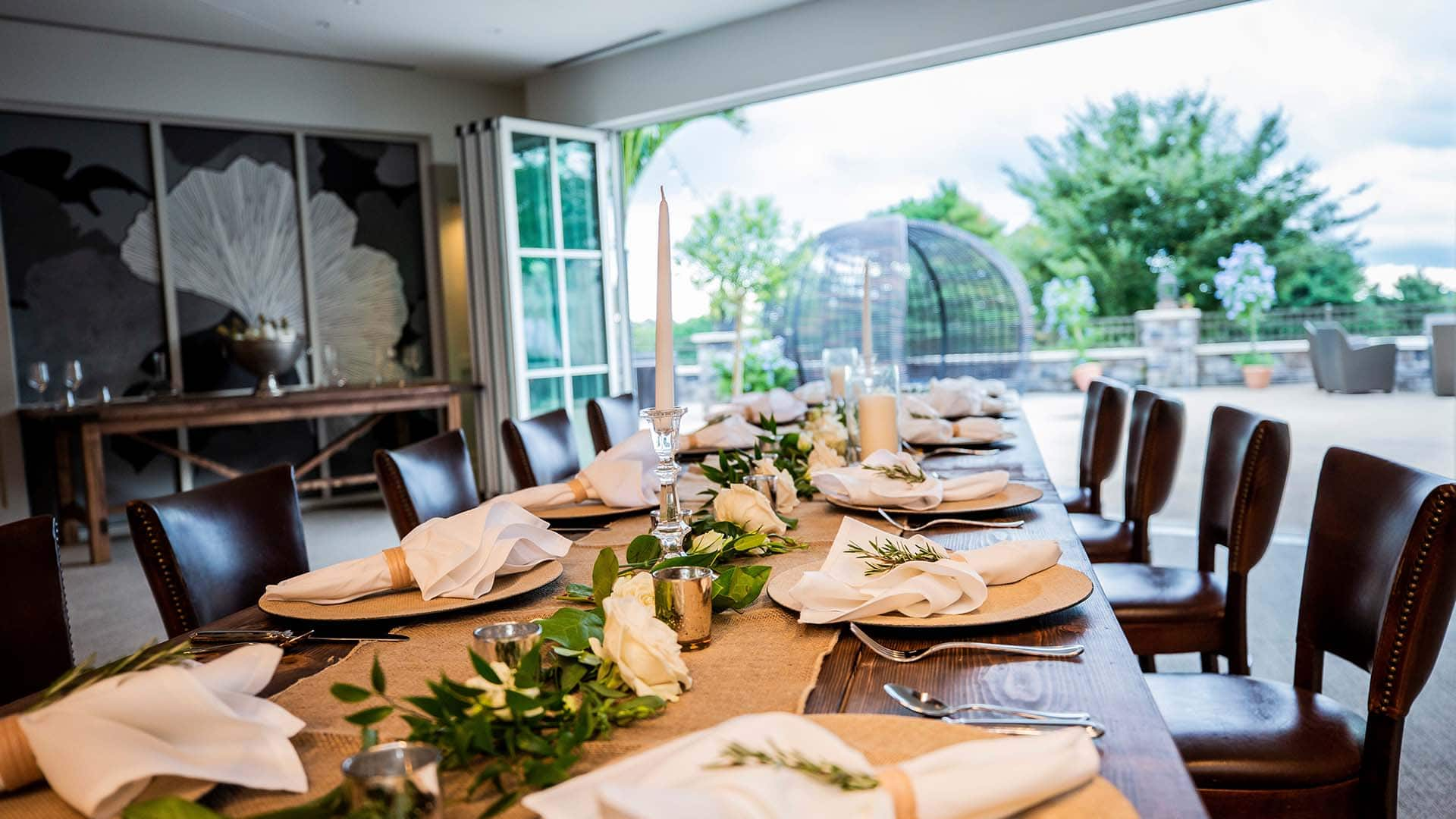 Private dining room with wooden feast table and plate settings with open patio in the background.